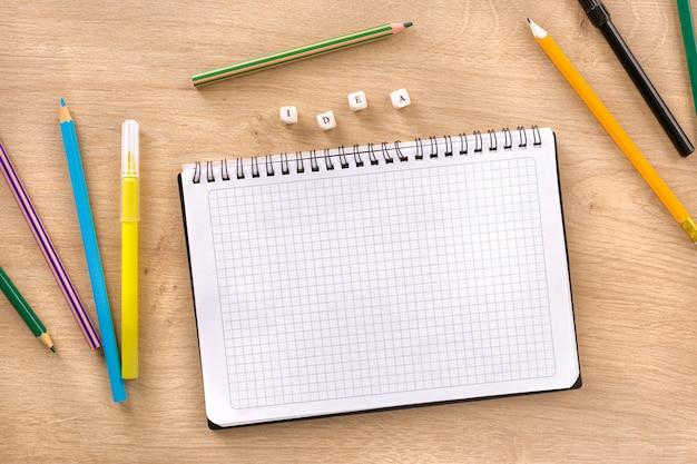 Escritorio de oficina con cuaderno, idea de palabra y marcadores de colores y vista superior de lápices