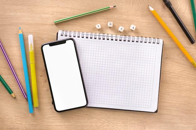 Escritorio de oficina con cuaderno, teléfono inteligente, idea de palabra y vista superior de marcadores y lápices de colores