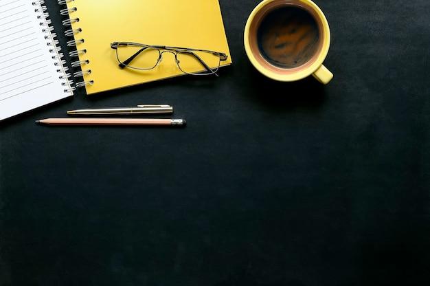 Escritorio de oficina de cuero oscuro con taza de café, bolígrafo, vasos y cuaderno amarillo