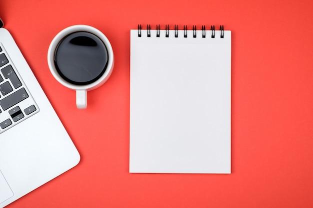 Escritorio de oficina de diseño con página de cuaderno en blanco y portátil