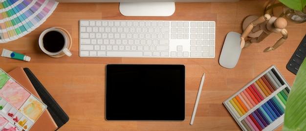 Escritorio de oficina de diseño con tableta digital, computadora, herramientas de pintura y suministros de diseño.