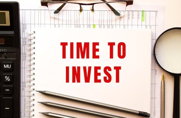 Escritorio de oficina con documentos financieros, lupa, calculadora, gafas. página de bloc de notas con el texto tiempo de invertir. vista desde arriba. concepto de negocio.