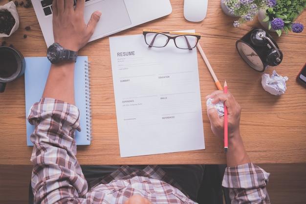 Escritorio de oficina con un empresario que llena un formulario de currículum, encuentra un trabajo, solicita trabajo en línea.