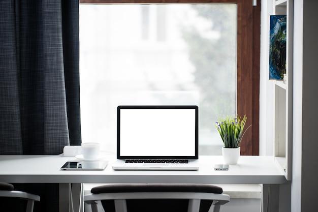 Escritorio de oficina junto a una ventana con computadora portátil y tableta y un teléfono inteligente