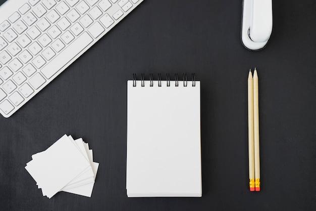 Escritorio de oficina con lápices, libreta, tarjetas y teclado