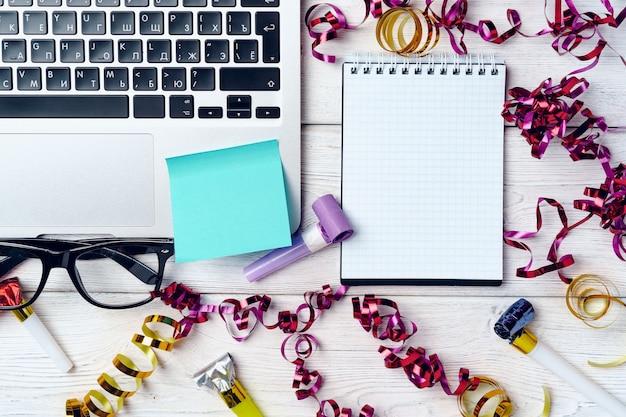 Escritorio de oficina con laptop y bloc de notas abierto decorado con serpentinas de fiesta. concepto de resoluciones de año nuevo