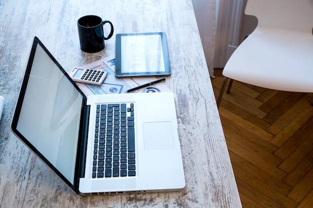 Un escritorio de oficina de madera con una computadora portátil y una tableta.