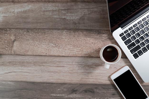 Escritorio de oficina de madera con computadora y teléfono inteligente con taza de café