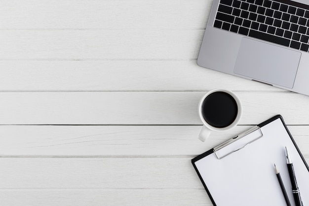 Escritorio de oficina de madera plano, vista superior. espacio de trabajo con portapapeles en blanco, portátil, bolígrafo, taza de café, suministros de oficina con espacio coppy sobre fondo de mesa de madera blanca