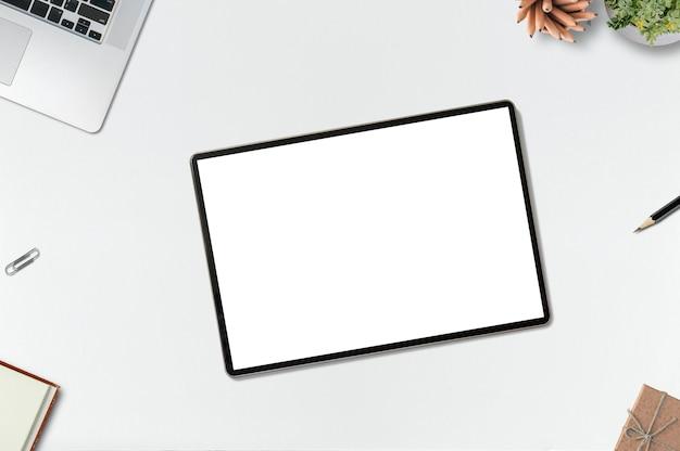 Escritorio de oficina de maqueta con tableta de pantalla en blanco, computadora portátil y suministros