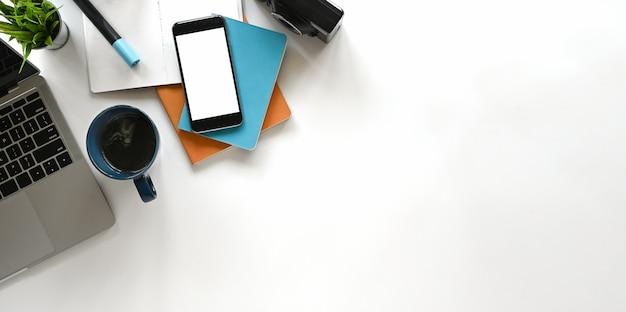 El escritorio de oficina moderno incluye computadora portátil, cámara, taza de café, cuaderno, libro, planta en maceta y lápiz.