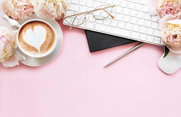 Escritorio de oficina de mujer plana vista superior con flores. espacio de trabajo femenino con laptop, flores peonías, accesorios, notebook, vasos, taza de café sobre fondo rosa.