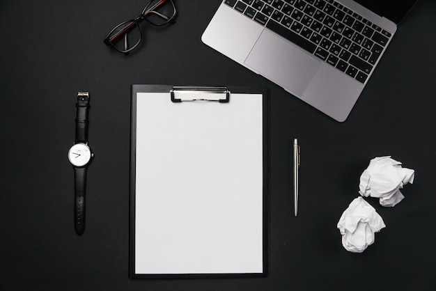 Escritorio de oficina negro con hoja de papel blanco con espacio de copia libre y bolígrafo, computadora portátil, gafas, reloj y bolas de papel arrugado.