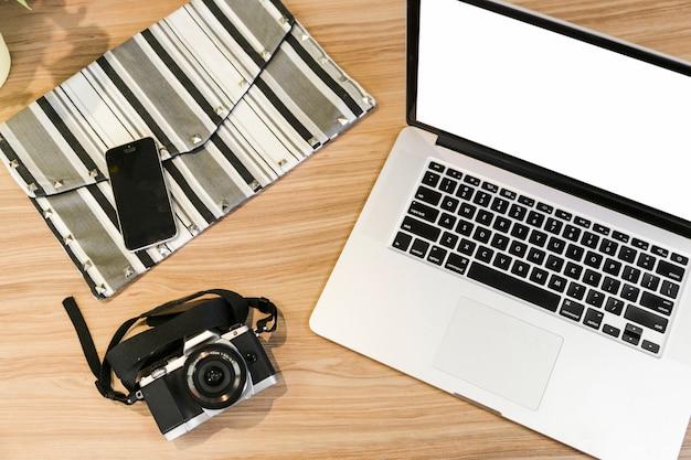 Escritorio de oficina con ordenador portátil y una cámara de foto
