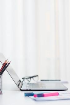Escritorio de oficina con ordenador portátil y unas gafas