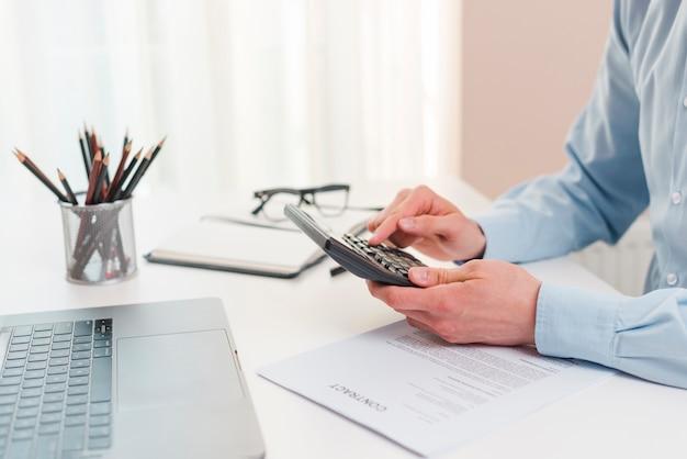 Escritorio de oficina con ordenador portátil y hombre de negocios