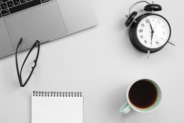 Escritorio de oficina con ordenador portátil y un reloj
