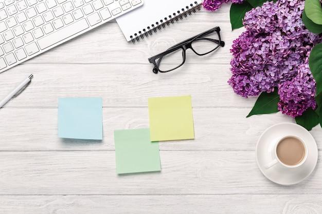 Escritorio de oficina con un ramo de lilas, taza de café, teclado, cuaderno y pegatinas de colores en pizarras blancas