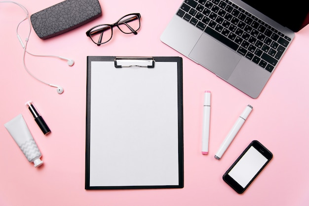Escritorio de oficina rosa para mujeres con una hoja de papel limpia con espacio de copia libre, computadora portátil, teléfono con pantalla en blanco, crema, lápiz labial, auriculares, anteojos y suministros de fondo.