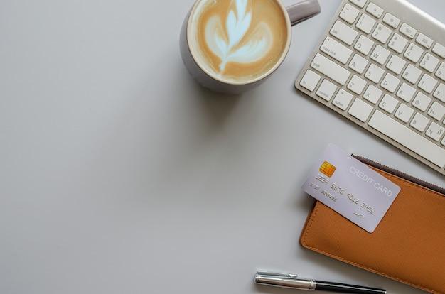 Escritorio de oficina con teclado, computadora, bolígrafo, café y tarjeta de crédito sobre fondo gris. vista superior con espacio de copia. concepto de negocios y finanzas