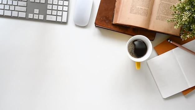 Escritorio de oficina con teclado, taza de café, libros, notas y lápiz, todo esto se coloca en el escritorio de oficina moderno.