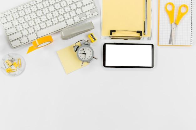 Escritorio de oficina con teclado y teléfono móvil.