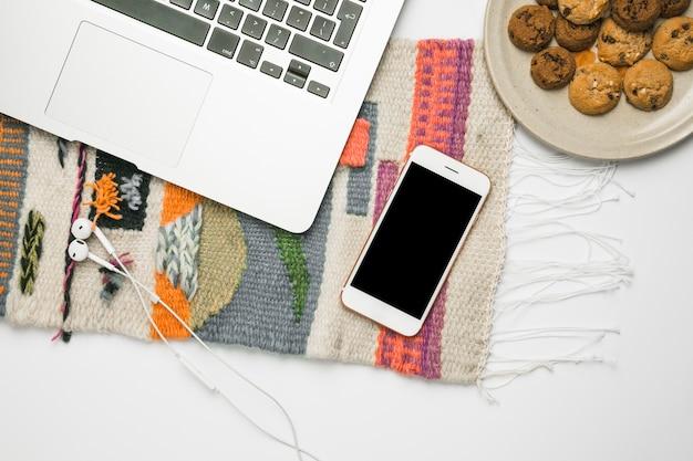 Escritorio de oficina con teléfono móvil y galletas
