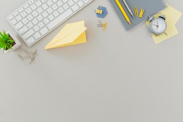Escritorio de oficina de vista superior con teclado y planta