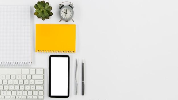 Escritorio de oficina de vista superior con teléfono móvil y planta