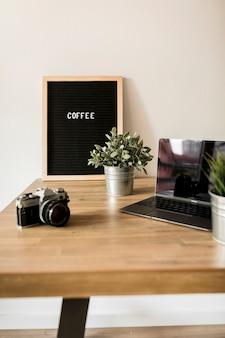 Escritorio con ordenador portátil y cámara de fotos
