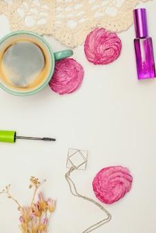 Escritorio plano con café, zephyr, cámara vintage y cosméticos.