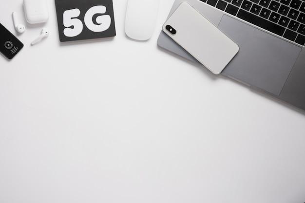 Escritorio plano con teléfono en la computadora portátil y texto de 5 g