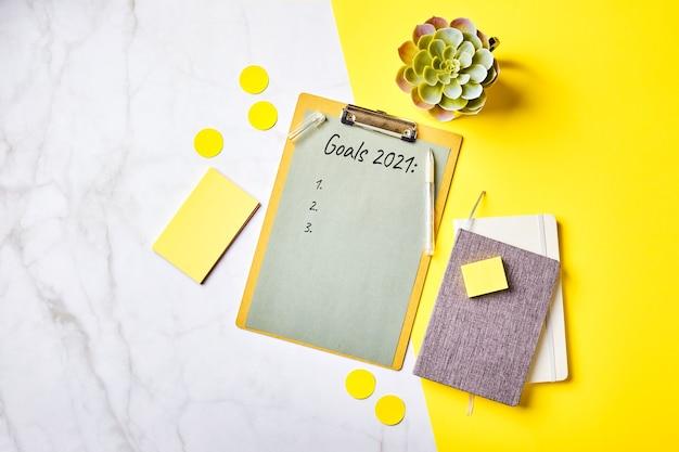 Escritorio con portapapeles con maqueta de lista de objetivos y material de oficina. oficina en casa, planificación del concepto de establecimiento de objetivos. flatlay, vista superior