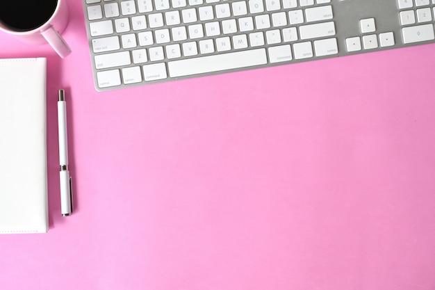 Escritorio rosa con espacio para computadora y copia.