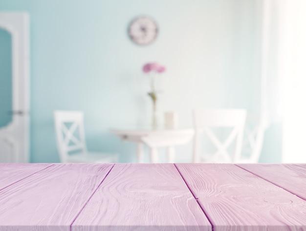 Escritorio rosa en primer plano con mesa de comedor borrosa en el fondo