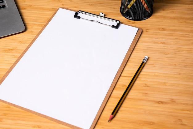 Escritorio sencillo de madera con portapapeles y bolígrafo.