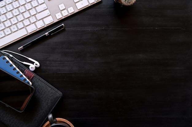 Escritorio superior de madera oscura con accesorios de oficina y espacio de copia.