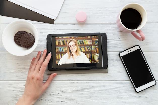 Escritorio con tableta, teléfono, café y galletas, profesor en la ventana de un reproductor multimedia