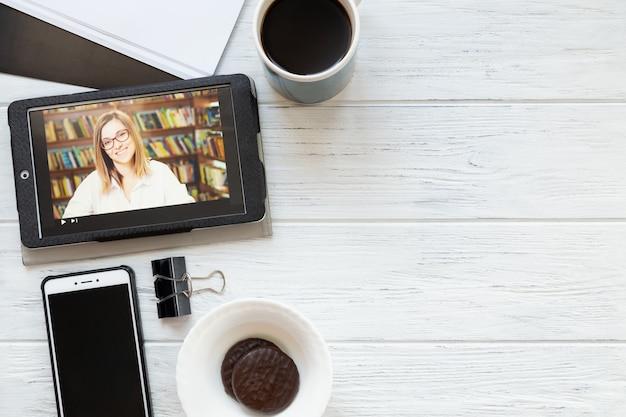 Escritorio con tableta, teléfono, café y galletas, vista superior con espacio de copia. escuela en línea, educación virtual, e-learning.