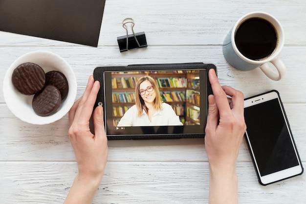 Escritorio con tableta, teléfono, café y galletas, vista superior. una mujer mira un video educativo.