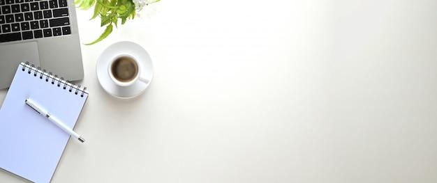 Escritorio de trabajo blanco que está rodeado de computadora portátil, bolígrafo, nota, planta en maceta y taza de café.