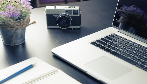 Escritorio de trabajo creativo con notebook y cámara vintage.