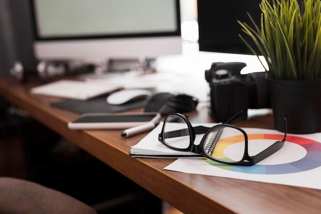 Escritorio de trabajo de primer plano con anteojos