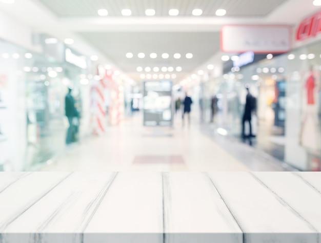 Escritorio vacío blanco frente a centro comercial iluminado borroso