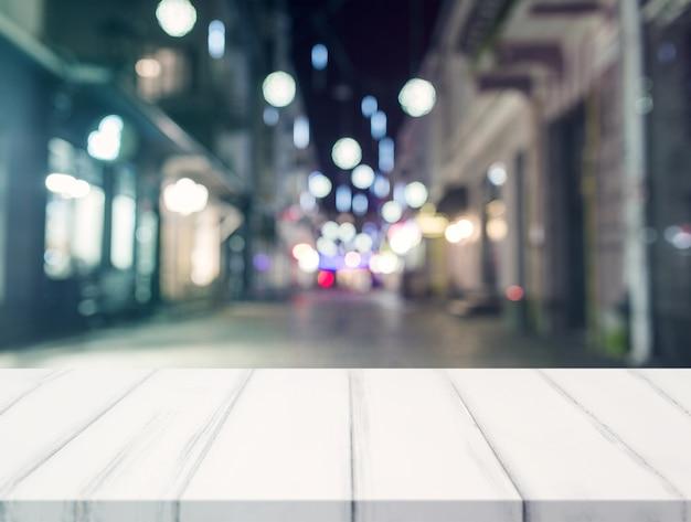 Un escritorio vacío frente a centro comercial iluminado borroso