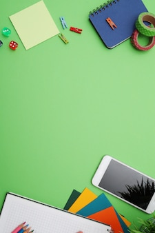Escritorio verde con papelería, vista superior, espacio de copia