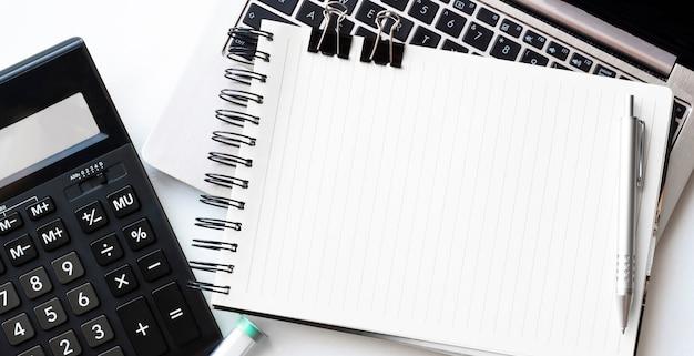Escritorio de vista superior con calculadora, lápiz y planta en maceta sobre fondo blanco.