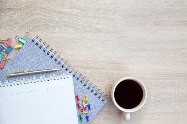 El escritorio de la vista superior y el calendario en blanco con un bolígrafo y equipo de oficina.