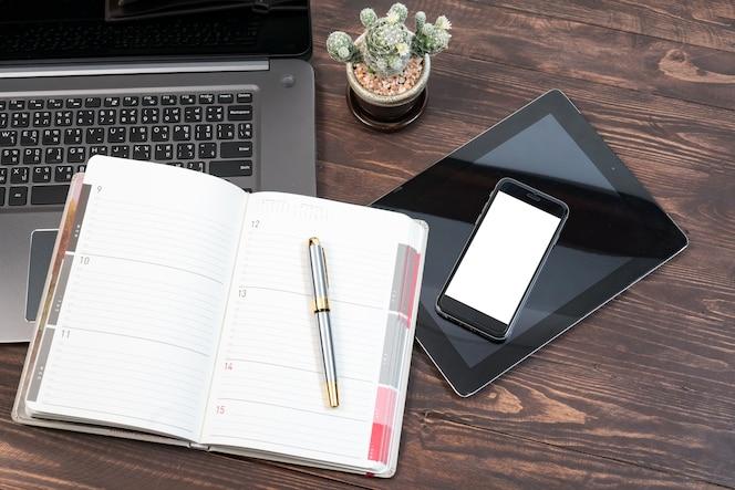 Escritorios modernos con computadoras portátiles, teléfonos inteligentes y otros accesorios.