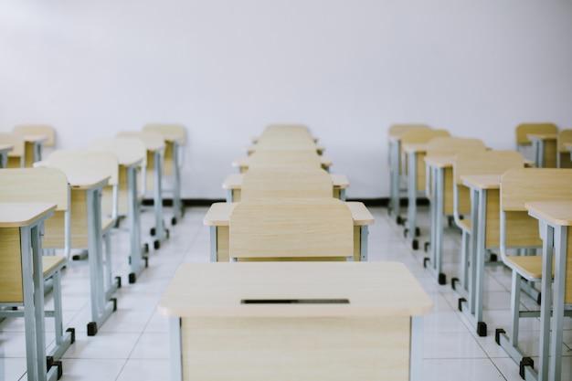 Los escritorios y sillas de los estudiantes están ordenados en el aula.